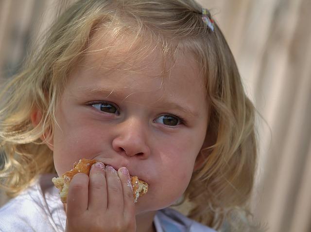 女の子が食べ物を口に運んでいる画像