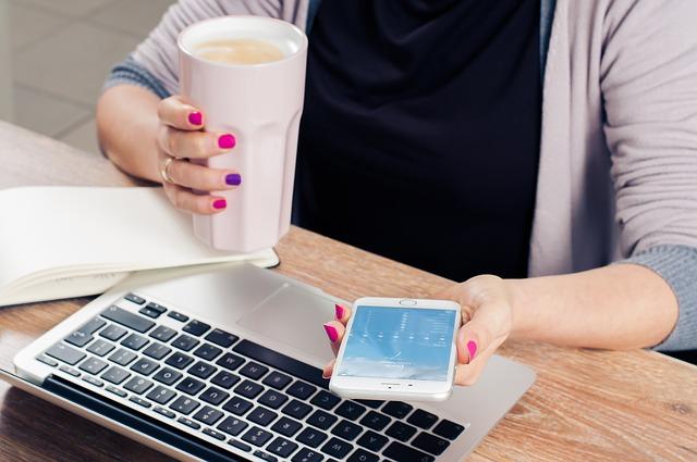 コーヒーとスマホを手にする女性画像