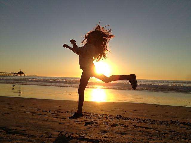 女性が浜辺でジャンプしている画像