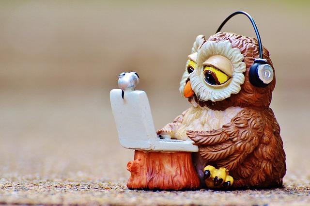 ヘッドフォンを付けながらパソコンをしているフクロウの画像