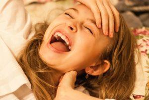 大きく口を開けて笑う少女