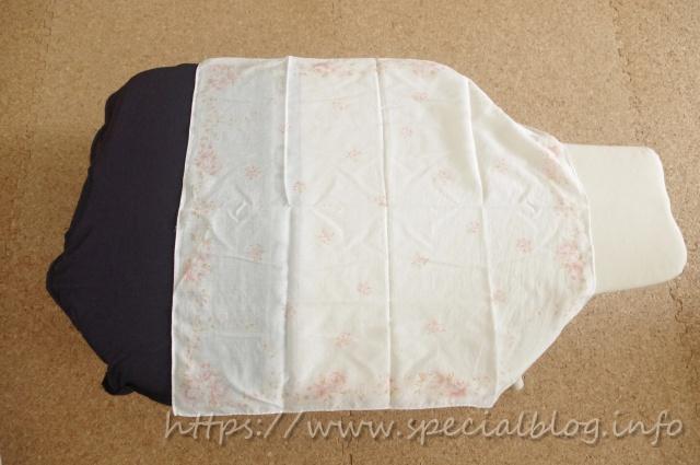 アイロン台に履かせてゴムを伸ばした状態のパンツにあて布を被せているところ